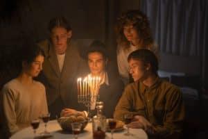 משפחה יושבת יחד סביב שולחן ועליו חנוכייה דולקת
